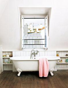 La gran bañera exenta con grifería de estilo antiguo es la protagonista del baño principal. A ambos lados se crearon armarios para aprovechar la inclinación de la pared.