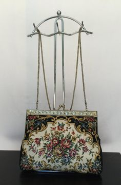 $45.00      Beautiful tapestry print chain bag with floral design. Embellished gold trim and 19-inch gold chain. Chain can be placed inside bag to be