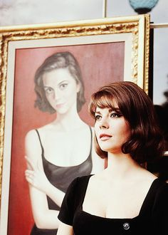 Natalie in #black posing with a portrait of herself