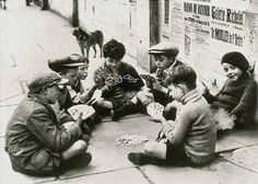 Homeless children playing cards on sidewalk, 1940s