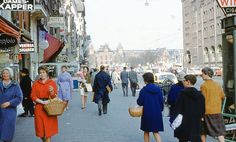 """1962. A view of Damrak in Amsterdam. The Damrak is an avenue and partially filled in canal in the center of Amsterdam. It is located between Centraal Station and Dam Square and is the main street where people who have arrived by train at Central Station enter the city. Because of the former stock exchange building, the Beurs van Berlage, erected there in the early 20th century, the term """"Damrak"""" has come to be a synonym for the Amsterdam Stock Exchange. #amsterdam #1962 #Damrak"""