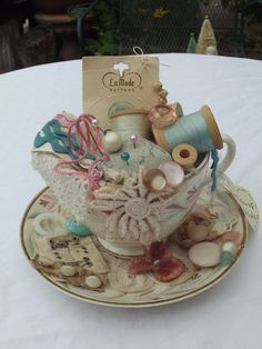 This is a sweet little vintage tea cup filled with vintage sewing notions. It has a pin cushion, spools of thread, lace, buttons, beads, vintage