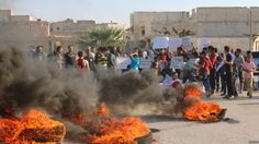 FILE - People gather near burning tires during a demonstration against forces…