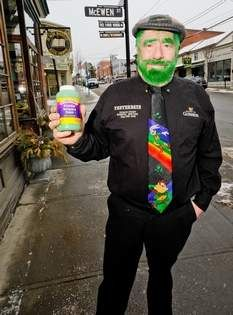 John Christison holds a bottle of green poster paint that he will use Monday night to paint a crooked line down Main Street in Warwick. It will be the 30th straight year that the Magical Leprechaun has done so to signify the start of St. Patrick's Day.