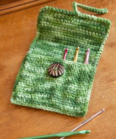 """The Case for Crochet Hooks - Great for crocheting on the go, this neat case features pockets to keep each of your hooks handy and scratch free. It's a super gift idea for your crocheting friends!         Finished Measurement: 6"""" x 7"""", folded closed  RHSS: 1 sk green tones. Hook: 5mm [US H-8].Button- ⅜"""" diameter, yarn needle. free pdf from Red Heart"""
