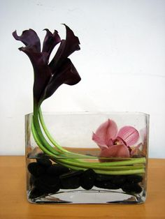 This is a floral arrangement that features eggplant miniature calla lilies with a single pink cymbidium orchid bloom.