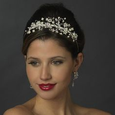 This bridal headpiece is accented with pearl and rhinestone floral vine sprays, and this wedding coronet is unique in its slightly off centered side design