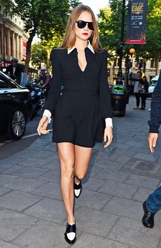 Cara Delevingne in a black dress, black and white loafers, and black sunglasses