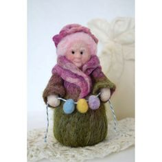 Granny is ready to help decorate for Easter. She is holding a pretty little Easter egg garland and is ready to adorn that little spot that needs a bit of color. I needle felted this nice granny entirely of wool. Her dress is of blended shades of greens, pinks and purples. Her ruffled