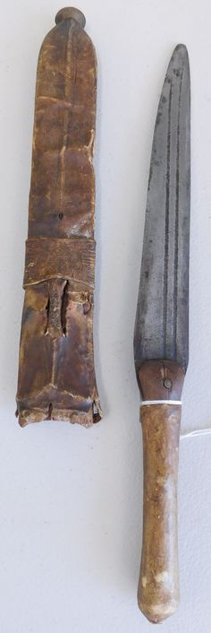 """129: African Knife & Sheath, circa 1900. Made of steel and rawhide, the item measures 14.75"""" x 1.5"""". Zulu, South Africa. Double-edged knife. Condition: Worn, see images. Shipping: $24.50 w/insurance and signature, due to length."""