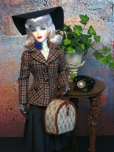 "1940's The jacket, gloves, and blouse are paired with the charcoal grey, pleated skirt from Integrity's ""Daily Threads"".  A wool felt, scoop-brimmed hat from The Couture Touch perfectly complement Miss Marshall's restyled blonde wig cap borrowed from Phoenix Gene Marshall. The train case is from Ashton Drake's ""Fit For a Queen"".  JAdore Gene Marshall is a Fashion Doll Quarterly exclusive BJD by Mel Odom & JamieShow.  Set Credits:CED table Telephone from ""A Hot Day in Hollywood"" Accessory Set"