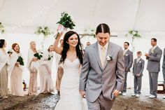 Funny, happy wedding exit. Bride raising bouquet. April. Outdoor. Idaho. Tent. Wedding. White. Gold. Green. Stella York. Mermaid Gown. Laughter. Applause. Gravel ground. Photo credit: Sloan Olivia Photography South jordan, Utah