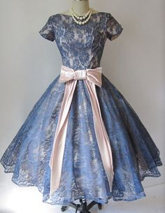 1950's cocktail party dress in the New Look silhouette, made of stormy blue lace over pale pink lining, with cap sleeves, pink satin bow, and full skirt with built-in crinoline layer. No maker label.