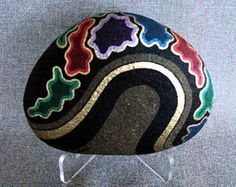 This is a large oval river rock that I have created into a unique 3-d work of art. The painted rock has a black background with streamers of rainbow colors on both sides. It can be rotated in different directions to present a variety of faces, as your mood dictates. The photographs show the front side and the back side, of the stone, in the different positions that you can display it. This is OOAK, One-of-a-Kind, you will own the only one. This make a beautiful home or office conversation…