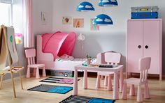 Kid's bedroom with white walls and a light pink bed, wardrobe and tables and chairs.