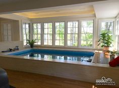 "The woodland view, tray ceiling with recessed lighting, and ""pickled"" white-wood finishing make this Endless Pool installation clean and serene."
