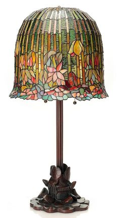 The Hanging Lotus Stained Glass Table Lamp was inspired by the Pond Lily (aka Water Lily or Hanging Lotus) lamps produced by Tiffany Studios in the early 1900s. The bronze toned base has a intricate d