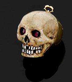 Memento mori pendant in gold with enamel and ruby eyes