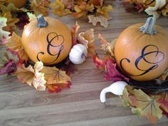 Pumpkin center pieces with monogram letter sitting on mini wreath made from fall garland ...then make pumpkin puree when done using them for event :)