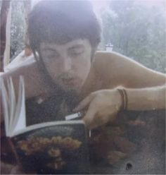 """A rare photo of Paul McCartney reading from John Lennon's """"In His Own Write,"""" 1966."""