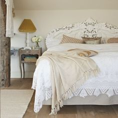 Neutral French-style bedroom  This bed is dressed with layers of lace, fringed throws and heaps of crisp broderie Anglais-edged pillowcases to create a gorgeous French-style bedroom. An ornate carved headboard adds detail to the neutral-toned walls