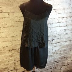 Olive + OAK ADORABLE BLACK SHORTS ROMPER This a is such a cute and trendy piece that looks like 2 pcs but is actually a romper. Thin spaghetti straps and pull on entry. 100% polyester Olive & Oak Shorts