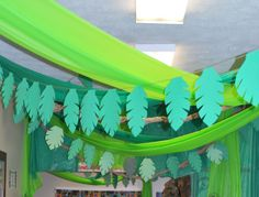 rainforest or jungle themed VBS - vines are made from plastic table cover rolls, and green yarn with construction paper leaves stapled to it.