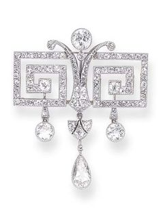 A BELLE ÉPOQUE DIAMOND BROOCH of Greek key design, set with small diamonds, suspending three large diamond pendants, mounted in gold and platinum, circa 1910, numbered.