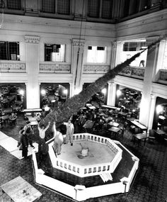 Workmen install a giant 45-foot-tall Christmas tree in the Marshall Field's Walnut Room on November 20, 1959...
