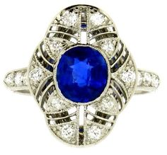 Sapphire and diamond cluster ring by Black Starr & Frost, circa 1920. Ornate pierced out cluster ring set to centre with an oval old cut sapphire weighing approximately 1.10ct in a millegrained rub-over setting.