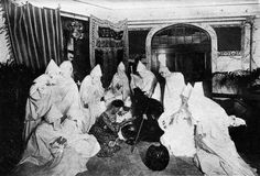 A group of people dressed as ghosts attend a fortune telling/seance party. From The Book of Halloween, 1919.