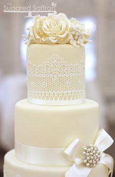 Torta de boda decorada con encaje, cintas, flores de azúcar y broche de perlas. #TortaDeBodaVintage