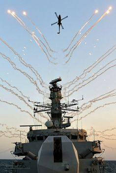 HMS Monmouth's Lynx Mk 8 helicopter creates a stunning backdrop of decoy flares during a test of her countermeasures systems in the Middle East.