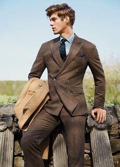 Man in brown tweed suit holds camel wool coat