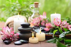 Cura con essenze vegetali, sassi zen in aromaterapia, candele e petali di fiori