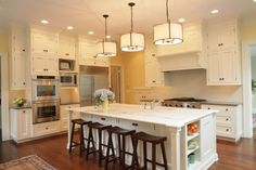 This all-white kitchen has a classic look with a slightly feminine style people love. The combination of the paneled cabinetry, marble counters, and classic pendants create a tasteful and restrained look.