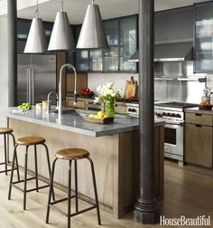 """When designer Robert Stilin saw this TriBeCa, New York, loft in an 1887 manufacturing building, he knew he would return it to its roots. A prior renovation had added uninspiring drywall and modern fixtures to a space that was never meant to be slick. Steel-wrapped cabinets, antiqued counters and vintage accessories were paired with professional appliances to give the kitchen """"instant age"""" while also standing up to the 21st-century demands of an urban family. Click through for more kitchen…"""