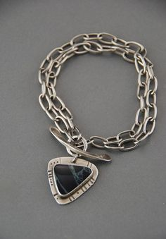 This simple bracelet features a bezel set Spiderweb Obsidian stone dangling as a charm off of a hand forged toggle clasp. The frame around the stone is