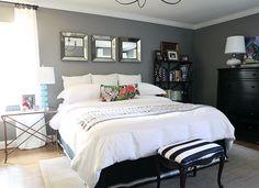 Grey accent wall, white bedding, espresso furniture