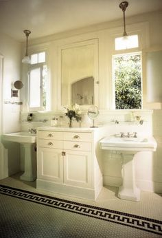 Classic white bathroom by Kevin Oreck with two pedestal sinks under windows flanked by built in bathroom cabinets and a white tile floor with a black border