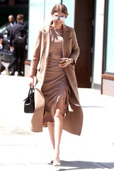 Gigi Hadid, showing how to be a dream babe in top-to-toe beige - including camel coat, court shoes and tie detail dress.