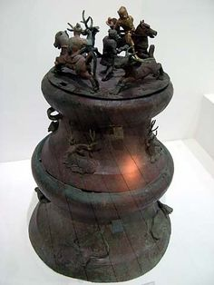 A bronze cowrie container, Western Han Dynasty (206 BC - 25 AD), Yunnan Provincial Museum, Kunming.  The bronze lid features a deer hunt with two horsemen and a standing figure decorates the top of the container. Below, on the sides of the container and its stand, are applied reliefs of deer and oxen.