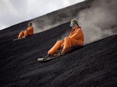 """Suited up in protective gear, tourists """"ash board"""" down Nicaragua's Cerro Negro Volcano. The activity is a highlight of an adventure travel tour that visits the volcano, the youngest in Central America. Photograph by Luca Zanetti, laif/Redux, May 2, 2014"""