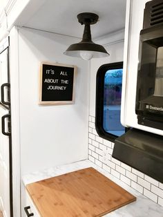 The kitchen workstation faces a window. Tagged: Kitchen, Marble Counter, Subway Tile Backsplashe, and Ceiling Lighting. Photo 16 of 16 in Hit the Road With This Chic Camper on Sale For $28K