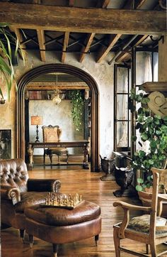 The walls are divine, the iron support system in the beams, distressed leather chair/ottoman paired with simple pine chair and absence of rugs reveal the yummy wood floor.