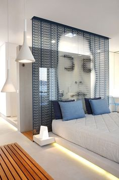 Paros Agnanti | Hotel in Parikia - Paros | Designed by A31 Archtecture: Behind the built in double bed, which seems to hover over a beam, is the glass wall-a contemporary piece of art-which distinguishes it from the walk in shower with phototherapy.