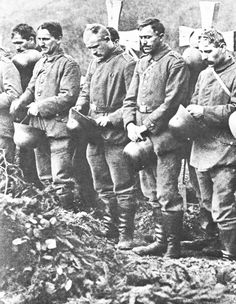 WWI; Helmets in hand, German soldiers pay respect to their fallen comrades. (Hoffschmidt and Tantum Collection)