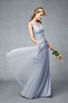 Dusty blue v-neck tulle gown with pleated bodice and dramatic skirt. Please schedule your appointment for bridesmaids dresses at J.J. Kelly Bridal. www.idoappointments.com