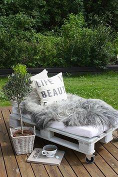 banquette jardin fabriquée avec palette bois peinte en blanc, pour le confort, un matelas fabriqué sur mesure et des coussins