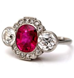 An Edwardian Ruby and Diamond Ring, English, circa 1910. Centring an oval-cut ruby within a single-cut diamond line surround, with millegrain set old brilliant cut diamonds to either side, mounted in platinum. #Edwardian #ring
